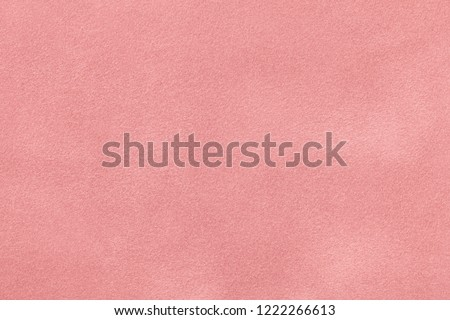Light pink matte background of suede fabric, closeup. Velvet texture of seamless pastel leather.