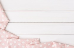 Light pink polka dots folded tablecloth over bleached wooden table. Top view image. Copyspace for your text