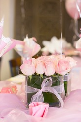 Light pink roses in glass vase table decoration center piece with balloons