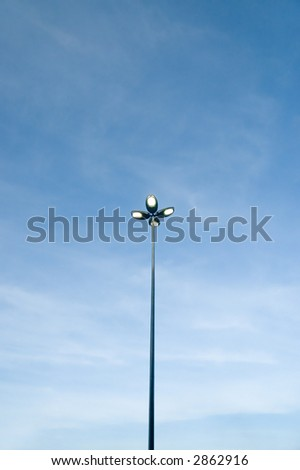 Light Pole with the lights on and blank blue sky
