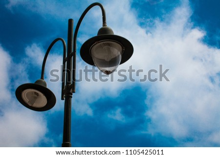 Light post with two bulbs and blue cloudy sky background. Outdoor street lights. Cast iron lamp. Large lanterns. Lighting pole. Illuminate. Electrical device #1105425011