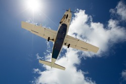 Light propeller-driven airplane flies in the blue sky. Bottom view of aircraft.