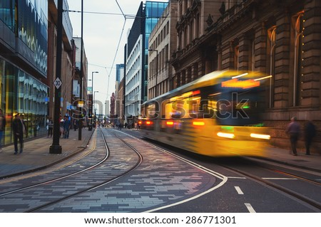 Light rail Metrolink tram in the city center of Manchester, UK in the evening. The system has 77 stops along 78.1 km and runs through seven of the ten boroughs