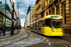 Light rail yellow tram in the city center of Manchester, UK in the evening. It is a popular transportation in Manchester.