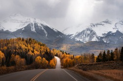 Light rays shine down on a scenic road in Colorado surrounded by mountains and fall colors. An autumn mountain scene near Mountain Village & Telluride, CO.