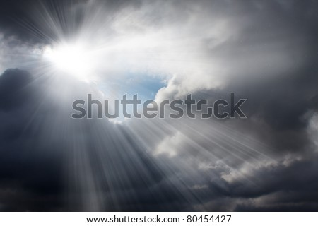 Light rays shine through the dark clouds