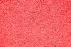 Light red color Background. Abstract stonewall backdrop. Stucco Wall painted in red coral color. Rough Surface plaster Texture. Beautiful Wallpaper with Copy Space for Design