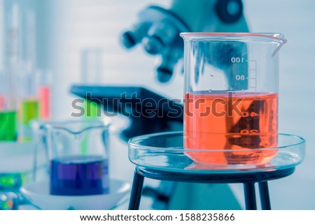 light red color liquid medicine in the glass beaker on the chemical tray with blurred liquid in beakers, test tubes, microscope in the Laboratory. Chemistry and science research concept.