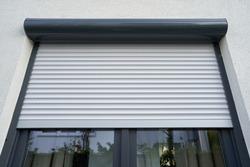 Light roller shutter curtains mounted on a dark window