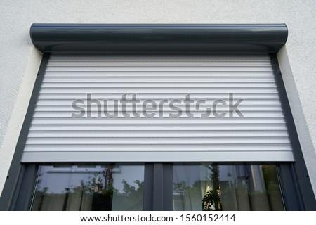 Light roller shutter curtains mounted on a dark window Stock photo ©