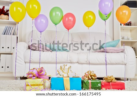 Light room with carpet on the floor and big sofa, gift boxes are on the carpet and birthday air balloons hang in the air
