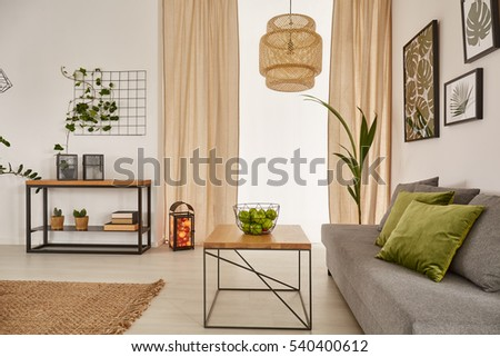 Light room with wooden table, grey sofa and chandelier #540400612