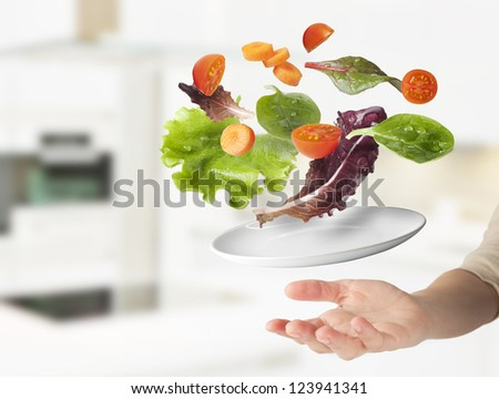 Light salad with floating vegetables. Vegetables in suspension on the kitchen