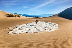 Light sand waves from the desert wind. Woman with a camera and a tripod goes among the dunes. USA. Mesquite Flat Sand Dunes, Death Valley, California. Concept of active and photo tourism