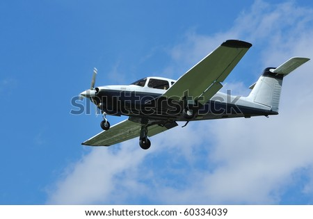 light 4-seater aircraft coming in to land. Piper Turbo Arrow IV with characteristic T-shape stabilator.