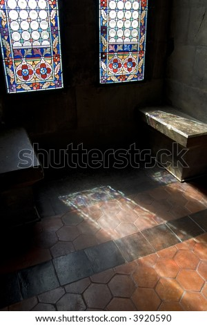 Light shines through a stained glass window onto a wooden floor in a medieval building.