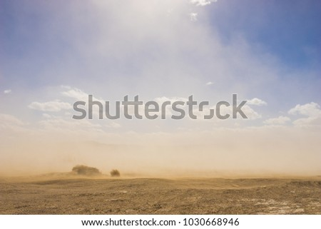 Light shines through the rising grains of a sandstorm in the vast hot desert.