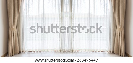 Light shines through white curtains in room