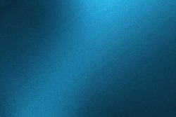 Light shining on blue metallic wall in dark room, abstract texture background