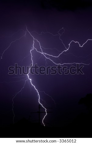 light, Sky with lightning bolt and silhouette of a roof and trees, close up - stock photo