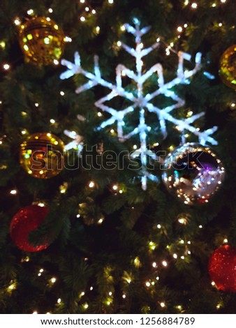 Light, snow-gown look adorned on a green Christmas tree. With gold bauble and red bauble.Blurry imaging #1256884789