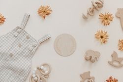Light soft baby pants with wooden toys and flowers. Fashion newborn, bohemian style, neutral beige colors. Flat lay, top view.