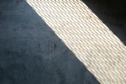 Light spilled through the steel wire of railings or baluster.Saw a shadow on raw concrete floor like net texture to strip of shadow on cement.