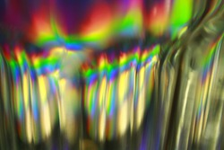 Light split into colours by a glass surface. Close up of glass with light interference effect, color diffraction. Transparent optical element that refract light.