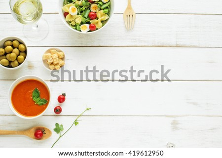 Light summer dinner / supper concept. Green salad with pasta, cherry tomato, quail eggs. Cold tomato soup (gazpacho), green olives and glass of cold white wine.