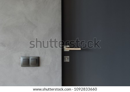 Light switch on the gray textured wall next to the door with metallic handle