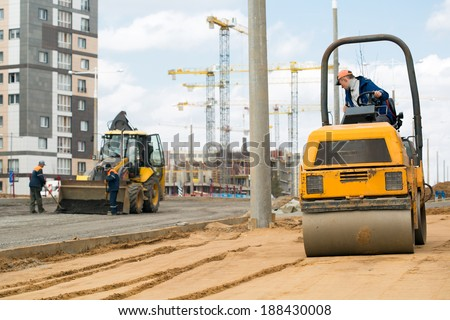 Light tandem vibratory roller compacting sand or soil during construction workers with shovels and tractor vehicle preparation road surface before laying an asphalt driveway