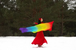 Light the fire! A dancing Japanese woman demonstrates energy in cold weather. A model with a long rainbow scarf dances in a snowy forest ot park. A person on dark green background.