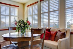 Light tones beautiful dining area  with a rustic dining table set, beige sofa and bright red pillows
