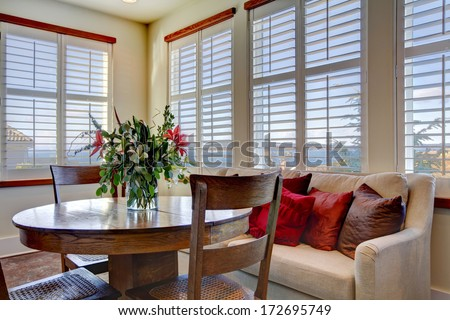 Light tones beautiful dining area  with a rustic dining table set, beige sofa and bright red pillows Stock photo ©