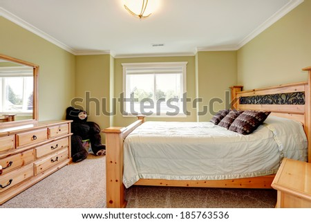 Light tones bedroom with lime walls and beige carpet floor. Furnished with queen size bed, dresser with mirror.