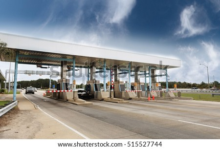 Light traffic at toll plaza under blue sky.