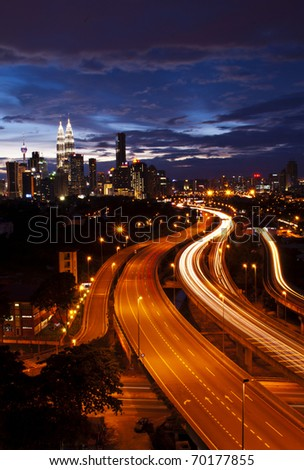 Light trail at busy highway with the view of kuala lumpur city