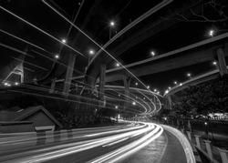 Light trail on street under Bhumibol Bridge in Bangkok, Thailand. Foreign text on the bridge is the bridge name