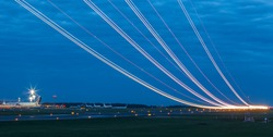 Light trails at airport runway, Against cloudy blue sky at dusk