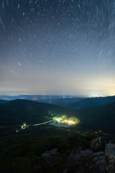 Light trails atop Sharp Top Mountain of Peaks of Otter looking down at the Peaks of Otter Lodge and Abbott Lake.