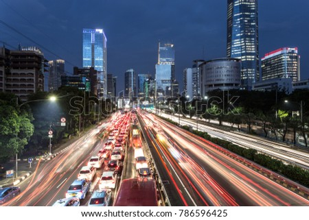 Light trails from heavy traffic along the Gatot Subroto highway in the heart of Jakarta business district at night. Jakarta is Indonesia capital city and the largest in Southeast Asia.