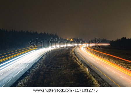 Light trails from the highway traffic in the hazy Rocky Mountains