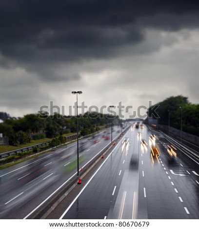 Light trails of motor vehicle traveling on a wet and slippery highway after a rainstorm against a overcast cloudy sky.