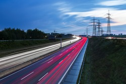Light trails on a highway freeway at sunset with power Pylons in the background