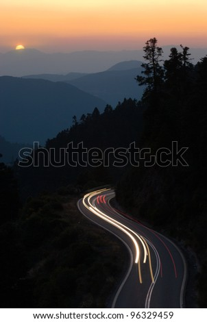 Continental Greece light trails on a winding road of mountain at sunset