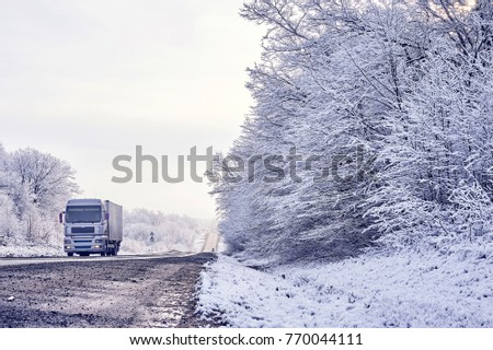light truck carries the load on a winter road along the forest