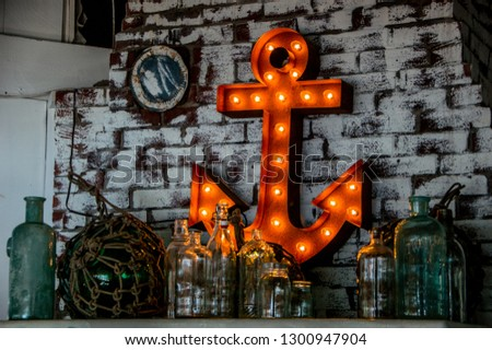 Light up anchor on a white brick wall. Picture contains nautical decorations at a restaurant in Maine. Great background photo for a website