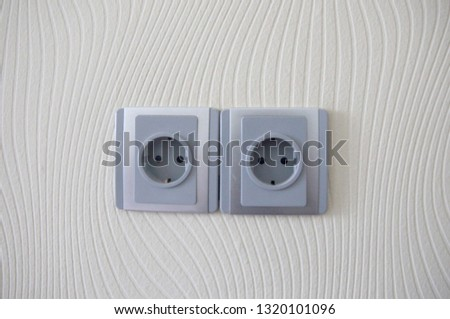 Light wallpaper on a wall with electrical outlet for background. Close Up detail