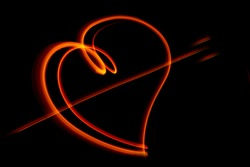 Light wave trail path, vibrant neon gold color in abstract swirls on a black background. Light painting. Heart shape