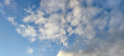 Light white cloud against the blue sky. A small, scattered white cloud floats across the sky next to the sun. The color of the sky changes from light blue to dark blue.